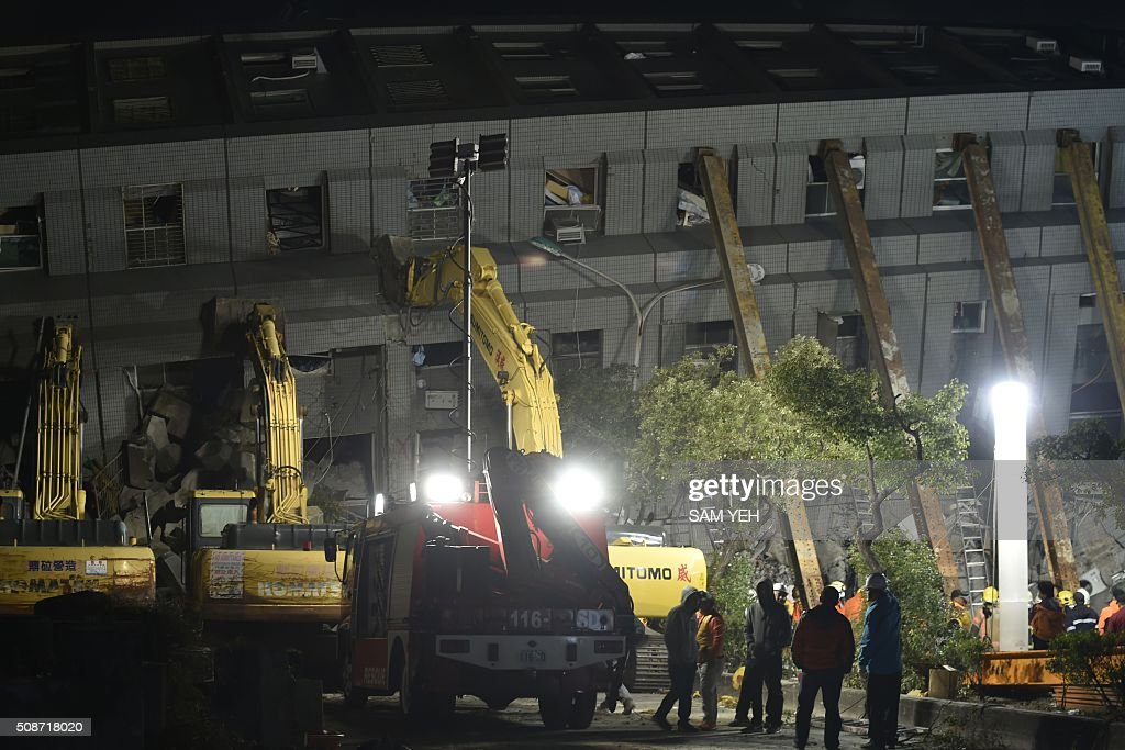 Rescuers and heavy machinery are seen at the site of a collapsed building in the southern Taiwanese city of Tainan on February 6, 2016 following a strong 6.4-magnitude earthquake. A powerful earthquake in Taiwan felled a 16-storey apartment complex full of families who had gathered for Lunar New Year celebrations in the early hours of February 6, with at least seven dead and more than 30 feared trapped. AFP PHOTO / Sam Yeh / AFP / SAM YEH
