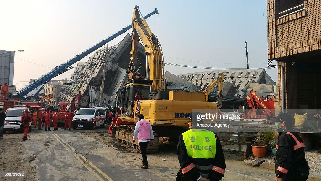 Rescuers and heavy machinery are seen at the site of a collapsed building in Yongkang District of Tainan, on February 6, 2016 following a strong earthquake struck Taiwan. At least 13 people including a baby girl were confirmed dead Saturday after a magnitude 6.4 earthquake hit southern Taiwan, collapsing buildings and injuring hundreds of others.