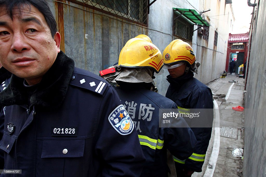 Rescuers and inspectors check the area around a private orphanage after a fire swept through the home for orphans and abandoned children in Lankao, in central China's Henan province on January 4, 2013. Seven children died and another was injured in the accident, local government and state media said. CHINA