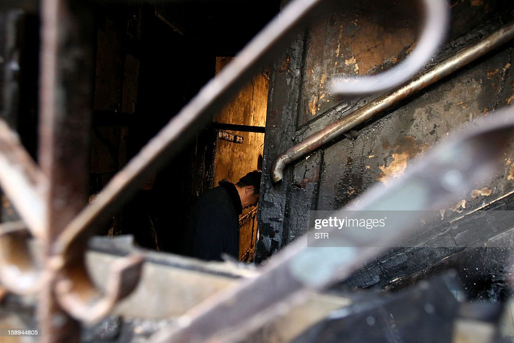 Rescuers and inspectors look over a burn area of a private orphanage where a fire swept through a home for orphans and abandoned children in Lankao, in central China's Henan province on January 4, 2013. Seven children died and another was injured in the accident, local government and state media said. CHINA OUT AFP PHOTO