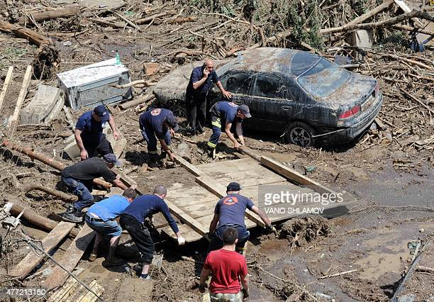 Rescuers and local residents collect debris at a flooded area in the Georgian capital Tbilisi on June 15 2015 Lions tigers and even a hippopotamus...