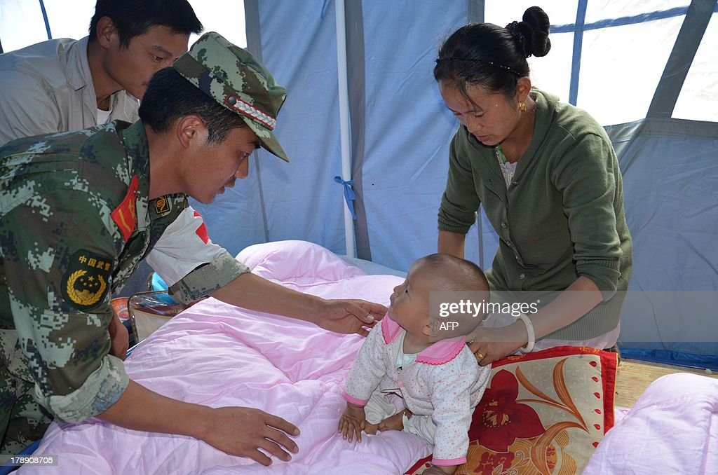 Rescuers and local residents take care of a baby following an earthquake in Deqin county, southwest China's Yunnan province on August 31, 2013. An earthquake on August 31 hit a remote part of southwest China near the popular tourist area of Shangri-La, killing four people and injuring over a dozen more, state media said. CHINA OUT AFP PHOTO