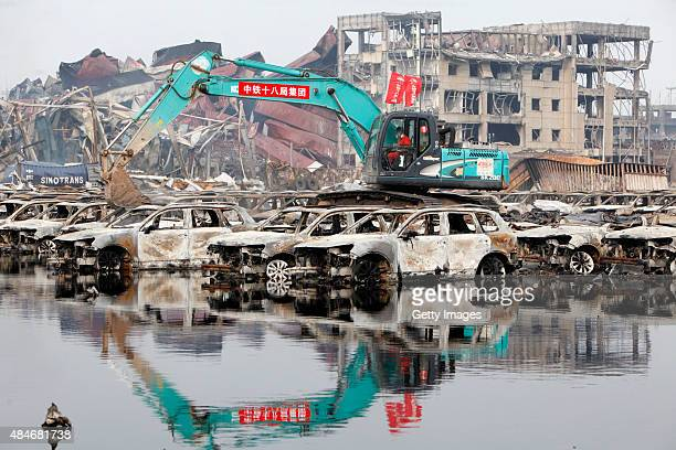 Rescuers and machines clean up burnt vehicles at the site of Tianjin warehouse explosion on August 20 2015 in Tianjin China The death toll from last...