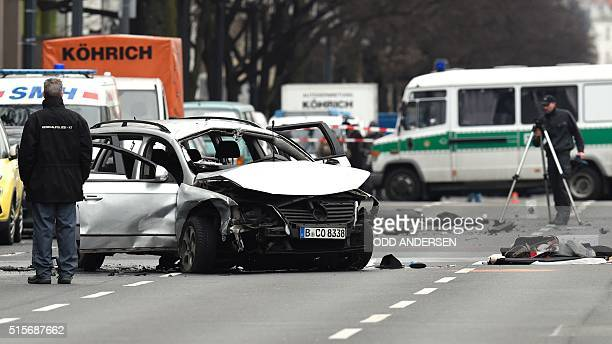 Rescuers and police officers work around a damaged car after a blast caused by an explosive device killed its driver travelling down a street in...