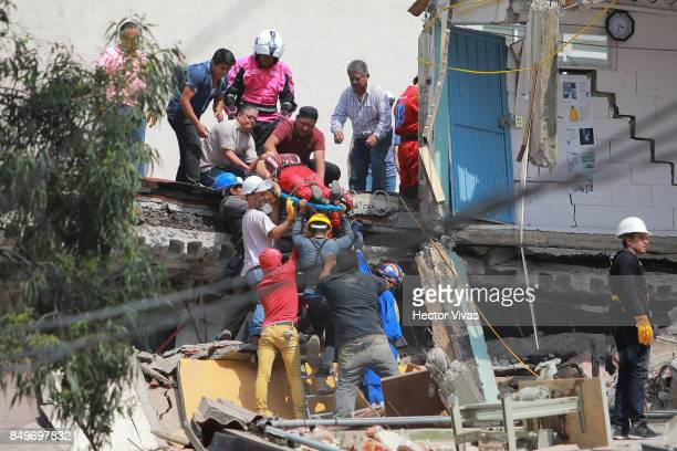 Rescuers and residents of Colonia Condesa carry a woman on stretcher amid the ruins of a building knocked down by a magnitude 71 earthquake that...