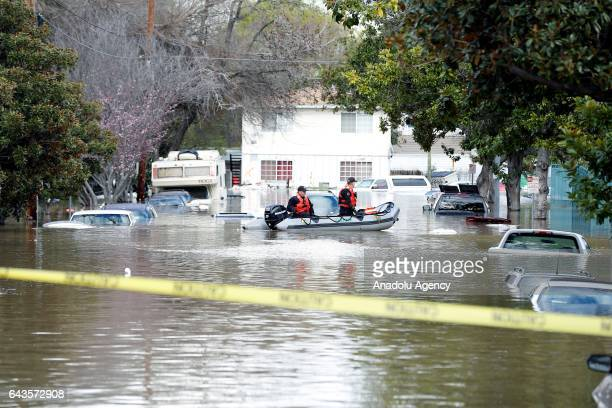 Rescuers are seen in a boat at a San Jose neighborhood inundated by water from an overflowing creek on February 21 2017 The flooded neighborhood sits...