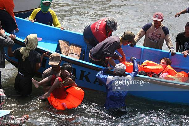 Rescuers assist survivors arriving on fishing boat at the wharf of Cidaun West Java on July 24 2013 after an Australiabound boat carrying...