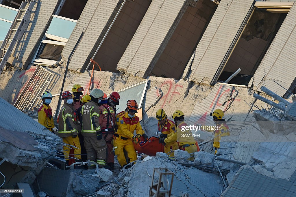 Rescuers bring out an eight-year old girl survivor to waiting personnel after she was rescued from the rubble at the Wei-Kuan complex which collapsed in the 6.4 magnitude earthquake, in the southern Taiwanese city of Tainan on February 8, 2016. Two survivors were on February 8 rescued from the rubble of an apartment complex in Taiwan felled by an earthquake, after being trapped for more than 50 hours. AFP PHOTO / Sam Yeh / AFP / SAM YEH