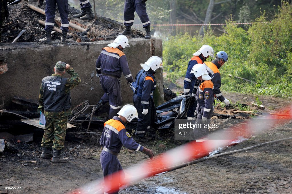 Rescuers carry a body bag with a victim of a fire near the charring remains of a burned out psychiatric hospital in the village of Luka in the northwest Russian Novgorod region on September 13, 2013. Thirty seven people were killed when a fire swept through a wooden psychiatric hospital in northwest Russia overnight yesterday, regional investigators said.