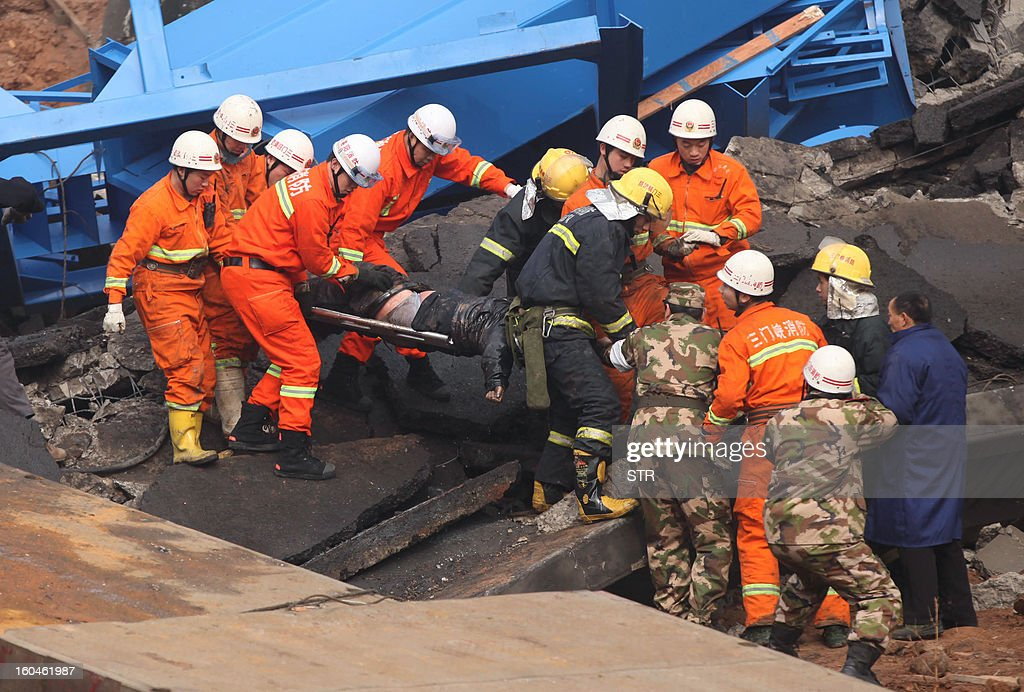 Rescuers carry a dead body (C) at the scene of the collapsed Yichang bridge near the city of Sanmenxia, central China's Henan province, on February 1, 2013 after a fireworks-laden truck exploded as it crossed the bridge killing 26 people as the structure collapsed and vehicles plummeted to the ground, state-run media reported. An 80-metre long part of the bridge collapsed and six vehicles had been retrieved from the debris, China's official news agency Xinhua said. The bridge near the city of Sanmenxia is on the G30 expressway, the longest road in China, which stretches for nearly 4,400 kilometres (2,700 miles) from China's western border with Kazakhstan to the eastern Yellow Sea.