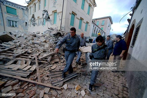 TOPSHOT Rescuers carry a man from the rubble after a strong earthquake hit Amatrice on August 24 2016 Central Italy was struck by a powerful...