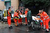 Rescuers carry a person injured on a stretcher after river burst their banks during heavy rainfall on November 4 2011 downtown Genoa The Italian...