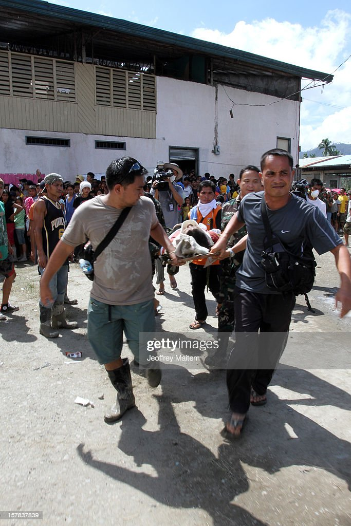 Rescuers carry a survivor in flood-hit village in the southern Philippine township of New Bataan, Philippines. More than 500 people have been killed and scores of others remain missing after Typhoon Bopha, the strongest storm to hit the Philippines this year, pounded the region.