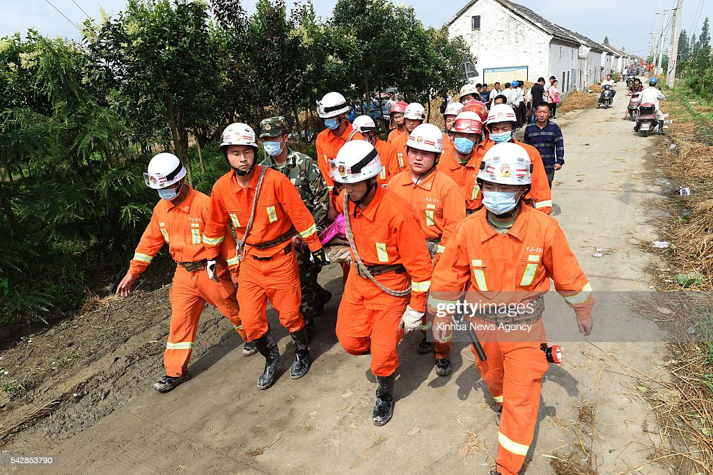 Rescuers carry a victim in Danping Village of Chenliang Township in Funing, Yancheng, east China's Jiangsu Province, June 24, 2016. A total of 98 people were killed after severe storms in several towns in Jiangsu on Thursday, local rescue headquarters said on Friday. About 846 people sustained injuries, 200 of whom were seriously wounded, it said. More than 8,600 houses, two elementary schools and eight factory buildings were damaged in the counties of Funing and Sheyang, and parts of Yancheng City along the eastern coast of China.
