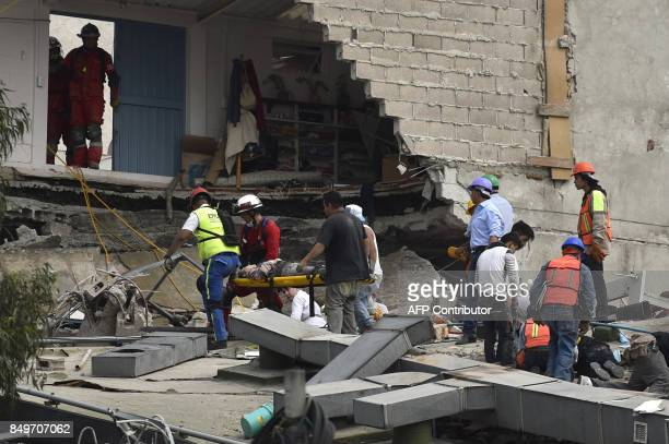 Rescuers carry a woman pulled out of the rubble on a stretcher as others hurry to free another person from the collapsed building after a quake...