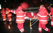 Rescuers carry an injured man who was in a van which was hit by a landslide on a highway between Salerno and Reggio de Calabre overnight on January...