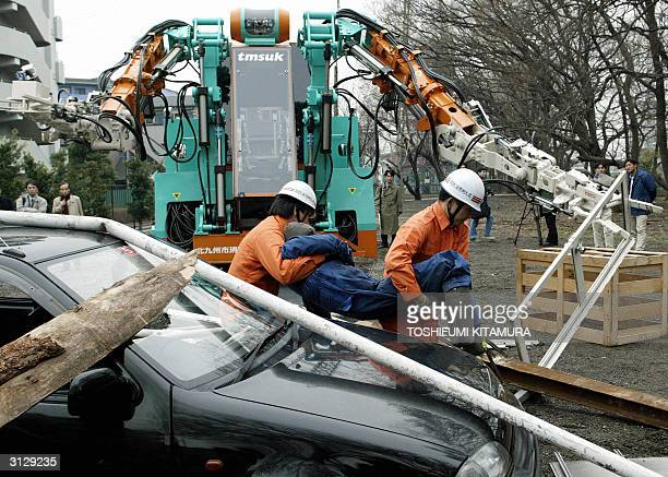 Rescuers carry an injured person from a car during a mock demonstration with Japan's largest rescue robot 'T52 Enryu' in Tokyo 25 March 2004 The...