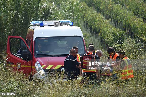Rescuers carry an injured person on a stretcher to a waiting ambulance on August 17 following a train crash near the French city of Montpellier A...