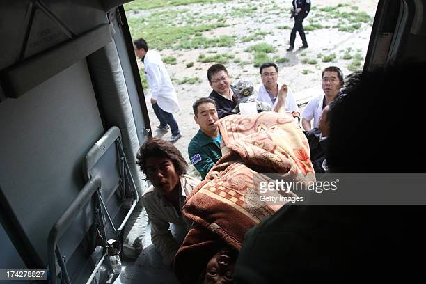 Rescuers carry an injured person onto a helicopter on July 23 2013 in Minxian China At least 89 people were killed and 5 others missing after a...