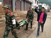 Rescuers carry an injuried child on a stretcher after a 61 magnitude earthquake hit the area in Ludian county in Zhaotong southwest China's Yunnan...