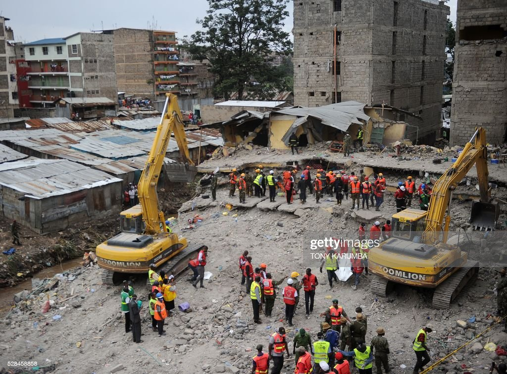 Rescuers carry away a body of a man retrieved from the rubble as efforts to evacuate a woman earlier discovered alive continue in the background, on May 5, 2016 in Nairobi, after she was trapped for six-days in the debris of a residential house that collapsed during torrential rain in Kenyan capital, Nairobi's low-income suburb of Huruma. The woman was pulled out hours after being located on May 5, 2016 morning by rescuers who gave her oxygen while they continued efforts to extract her from the ruins of the six-storey building. / AFP / TONY