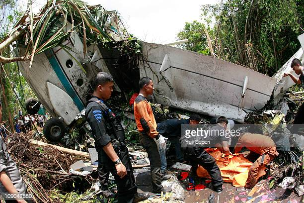 Rescuers carry the body of the Pilot Captain Fadlul Karim from the wreckage after the SMAC plane type Cessna 212 turbotrop crashed on February 13...