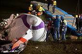 Rescuers check the wreckage of the TransAsia ATR 72600 on the Keelung river at New Taipei City on February 4 2015 At least 23 people were killed when...