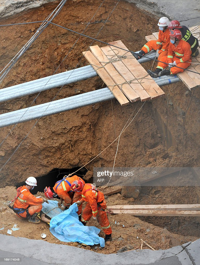 Rescuers (lower) cover a dead body found in a sinkhole on a road in Shenzhen, south China's Guangdong province on May 21, 2013. Five people died when a 10 metre (33 feet) wide sinkhole opened up at the gates of an industrial estate in Shenzhen, the southern Chinese boom town neighbouring Hong Kong, local authorities said on May 21. CHINA
