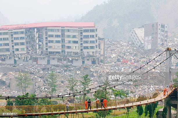 Rescuers cross a suspension bridge May 16 2008 in Beichuan China 50000 people are estimated to have been killed in the deadliest earthquake in China...