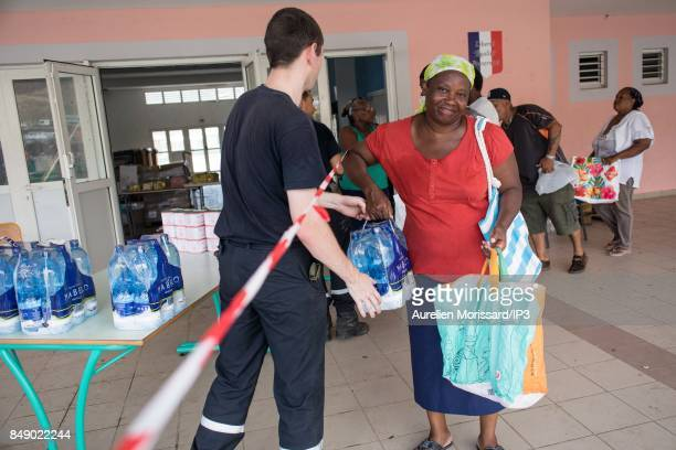 Rescuers distribute water at Saint Martin III's College in the Orleans neighborhood eleven days after the passage of hurricane Irma on September 16...