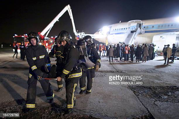 Rescuers evacuate a victim during an aircraft crash training at the Orly airport south of Paris on October 24 2012 AFP PHOTO KENZO TRIBOUILLARD