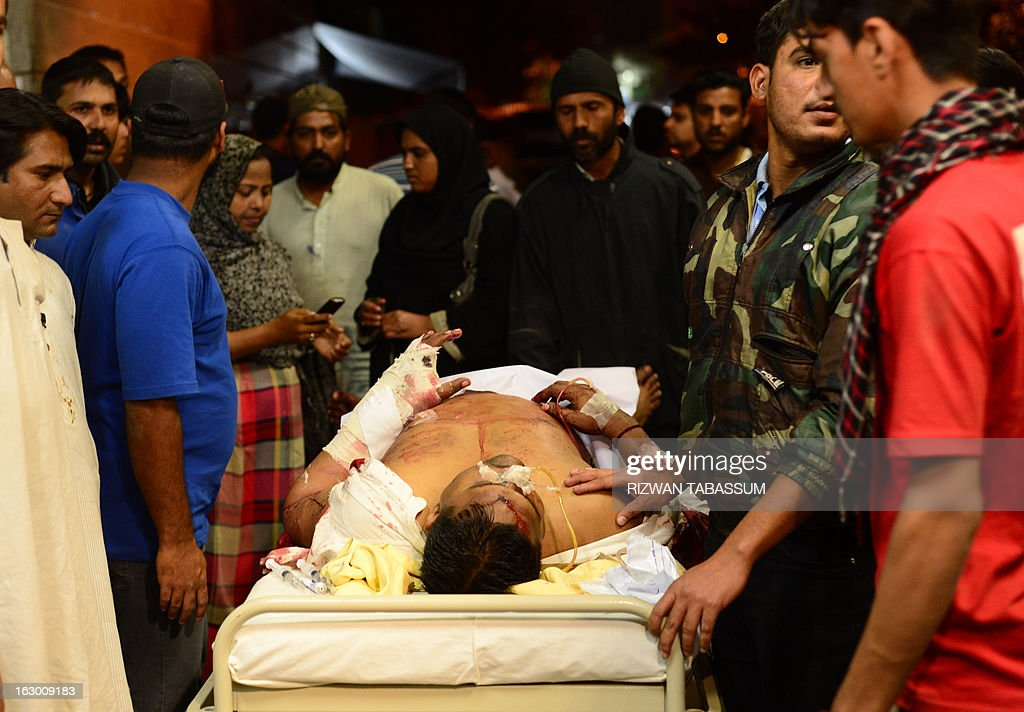 Rescuers evacuate an injured bomb blast victim after an explosion damaged two residential buildings in Karachi on March 3, 2013. A bomb attack in Pakistan's largest city Karachi on Sunday killed at least 23 people, including women and children, and wounded 50 others, police said. AFP PHOTO/Rizwan TABASSUM