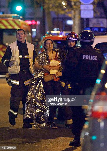 Rescuers evacuate an injured woman on Boulevard des Filles du Calvaire close to the Bataclan theater early on November 14 2015 in Paris France...