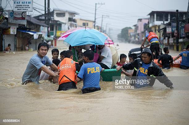Rescuers evacuate residents after a river overflowed flooding their homes due to heavy rains brought about by Tropical Storm FungWong in Tumana...