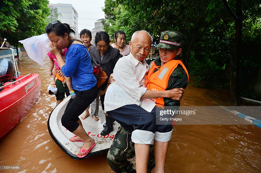 Rescuers evacuate residents from flood-hit areas on July 1, 2013 in Chongqing, China. A torrential rain hit Sichuan province on Monday, leaving five people dead and six missing.