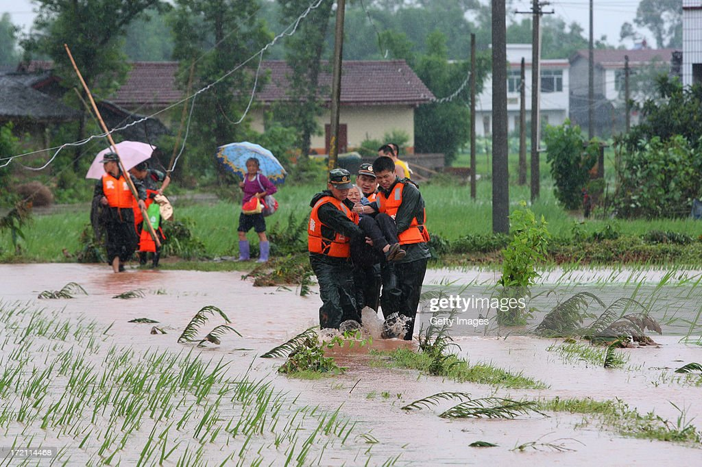 Rescuers evacuate residents from flood-hit areas on July 1, 2013 in Suining, China. A torrential rain hit Sichuan province on Monday, leaving five people dead and six missing.