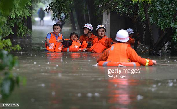 Rescuers evacuate residents from floodhit areas on July 9 2013 in Chengdu China At least one person was killed and 15 others missing after severe...