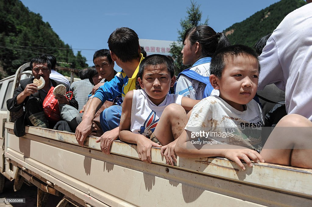 Rescuers evacuate residents in a truck on July 29, 2013 in Tianshui, China. At least 24 people were killed, with one person still missing, after rainstorm-triggered floods and landslides hit many areas of Tianshui city recently.
