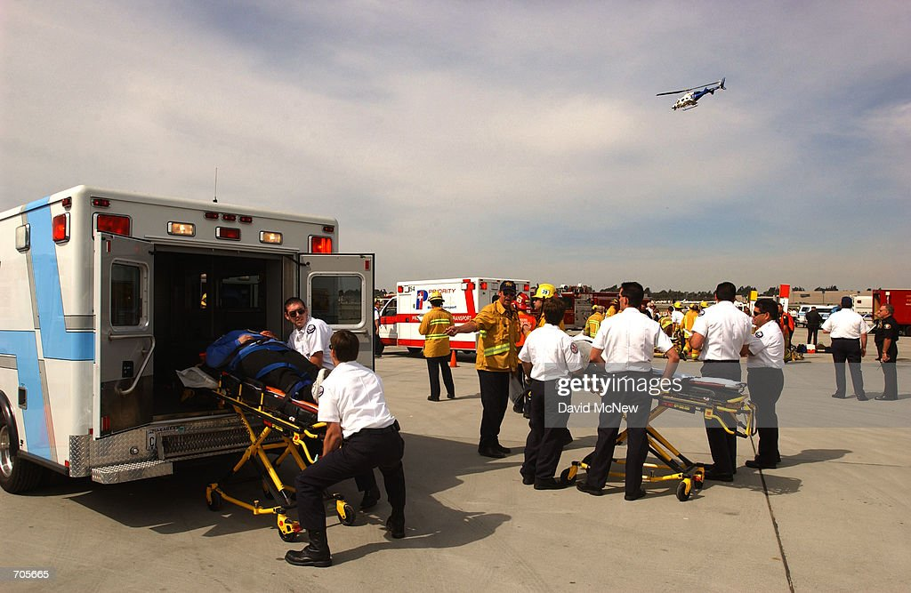 Rescuers evacuate 'victims' by ambulances and a helicopter during an FAArequired triennial emergency exercise at John Wayne Airport March 6 2002 in...