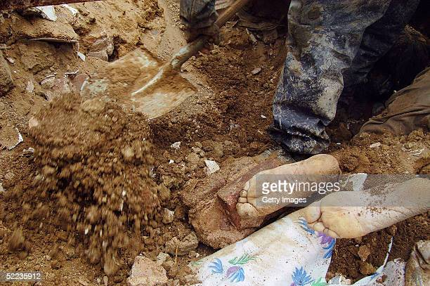Rescuers find the body of a young boy as they dig through the remains of collapsed buildings looking for survivors on February 24 2005 in the remote...