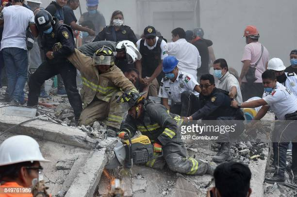 TOPSHOT Rescuers firefighters policemen soldiers and volunteers desperately remove rubble and debris from a flattened building in search of survivors...