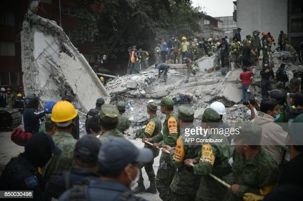 TOPSHOT Rescuers firefighters policemen soldiers and volunteers remove rubble and debris from a flattened building in search of survivors after a...