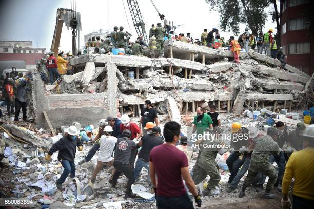 TOPSHOT Rescuers firefighters policemen soldiers and volunteers search for survivors in a flattened building in Mexico City on September 20 2017 a...
