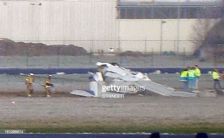 Rescuers gather around the crashed Cessna passenger plane at Brussels South airport in Charleroi, on February 9, 2013. It appears thatplane experienced problems on take-off and returned to the airport but crashed next to the runway as it attempted a landin./ Five people died in the accident. STRINGER