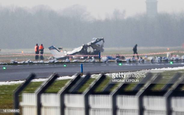 Rescuers gather around the crashed Cessna passenger plane at Brussels South airport in Charleroi on February 9 2013 It appears that the plane...