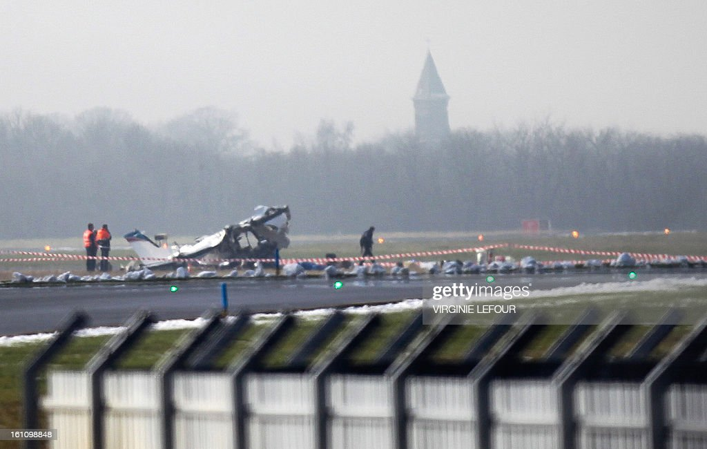 Rescuers gather around the crashed Cessna passenger plane at Brussels South airport in Charleroi, on February 9, 2013. It appears that the plane experienced problems on take-off and returned to the airport but crashed next to the runway as it attempted a landing. Five people died in the accident. AFP PHOTO / BELGA / VIRGINIE LEFOUR -