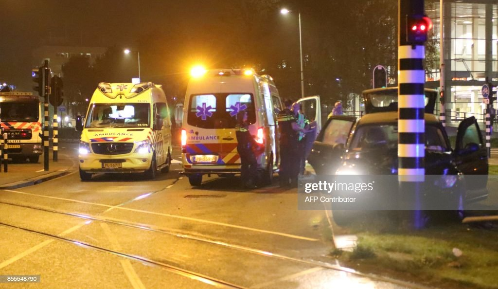 Rescuers gather on the scene of a car accident involving Manchester City's Argentine striker Sergio Aguero on September 28, 2017 in Amsterdam. Aguero 'sustained injuries' in a car crash in the Netherlands and is returning to Britain to be checked ahead of the weekend's Premier League fixtures, the club said on September 29, 2017. Aguero, 29, had been to a concert in the Dutch capital on his day off and suffered a broken rib in the smash, when the driver lost control of the vehicle on a bend and it struck a post. / AFP PHOTO / KaWijKo Media / Nickelas Kok