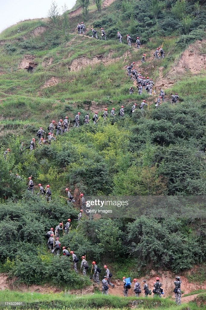 Rescuers head to the site of a mudslide at Tongxin village on July 23, 2013 in Minxian, China. At least 95 people were killed and more than 1,000 people injured after a 6.6-magnitude earthquake jolted the border of Minxian county and Zhangxian county in Gansu province on Monday morning.