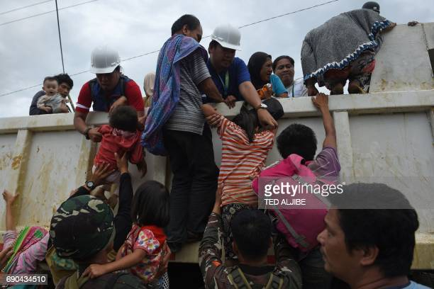TOPSHOT Rescuers help children onto a truck after they were rescued from their homes in a village on the outskirts of Marawi on the southern island...