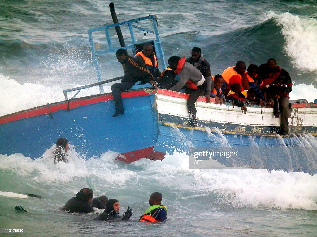 Rescuers help people in the sea after a boat carring some 250 migrants crashed into rocks as they tried to enter the port of Pantelleria an island...